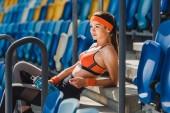 boční pohled šťastné mladé ženy relaxační na schodech na sportovní stadion