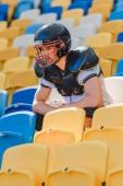 pohledný mladý americký fotbalista sedí na tribuny na sportovní stadion