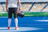Photo cropped shot of american football player with helmet standing alone at sports stadium