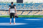 Fényképek rear view of american football player standing alone at sports stadium