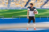 Fotografie athletic american football player standing alone at sports stadium