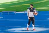 Fotografie attractive young american football player standing alone at sports stadium