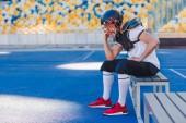 boční pohled mladých americký fotbalista držící klec helmy sedí na sportovní stadion