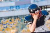 smutně mladý americký fotbalista sedí u sportovního stadionu