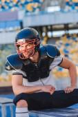 Fotografie pohledný mladý americký fotbalový hráč, sedící u sportovního stadionu