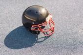 Fotografie high angle view of black american football helmet lying on asphalt