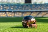 close-up shot of american football helmet lying on green grass of stadium