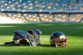Fotografie american football helmet with chest protection lying on green grass of stadium