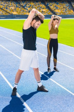 young couple of athletes warming up before training on running track at sports stadium