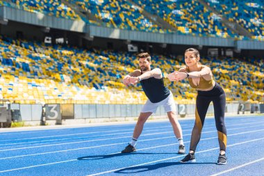young sporty couple warming up before training on running track at sports stadium