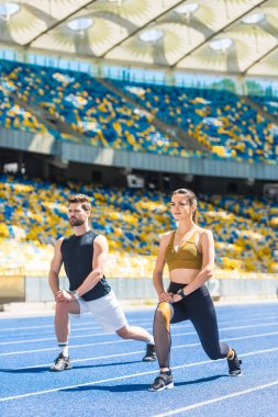 young athletic couple warming up before training on running track at sports stadium