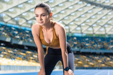 sportive young woman resting after jogging on running track at sports stadium