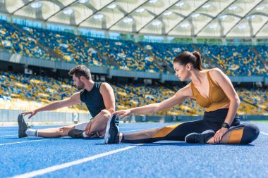 young athletic male and female joggers sitting on running track and stretching at sports stadium