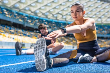young active couple sitting on running track and stretching at sports stadium