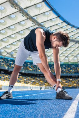 athletic young man stretching on running track at sports stadium