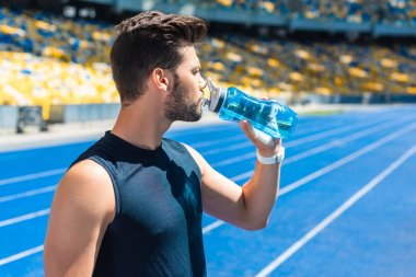 attractive young man drinking water after training at sports stadium