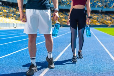 cropped shot of sportive couple with bottles of water on running track at sports stadium