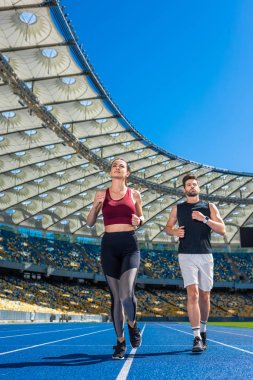 fit young male and female joggers running on track at sports stadium
