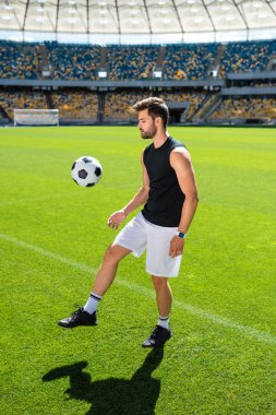 attractive young soccer player bouncing ball on leg at sports stadium