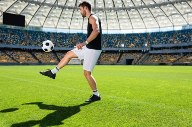 sporty young soccer player bouncing ball on leg at sports stadium