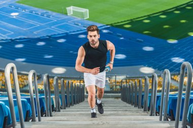 high angle view of attractive young man jogging upstairs at sports stadium
