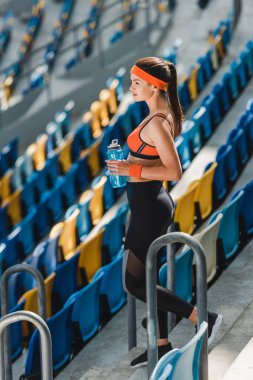 high angle view of beautiful young woman with water bottle standing on tribunes at sports stadium