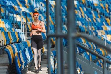 beautiful young woman walking by tribunes at sports stadium