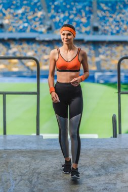 beautiful young woman in modern sportswear walking at sports stadium