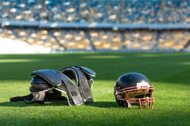 american football helmet with chest protection lying on green grass of stadium