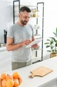 Fotografie glücklicher Mann mit digital-Tablette in der Nähe von Tisch in der Küche