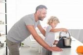 Fotografia vista laterale delluomo sorridente che sta vicino al figlio mentre lui usando il mixer per fare la pasta in cucina