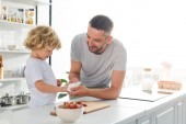 smiling father helping son to wiping hands by napkin near tabletop with strawberries at kitchen