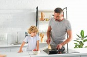 man heating frying pan while his son standing near at kitchen