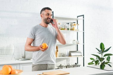 Front view of smiling man talking on smartphone and holding orange on kitchen stock vector