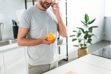 Cropped image of man talking on smartphone and holding orange on kitchen stock vector