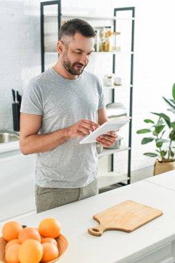 happy man using digital tablet near table on kitchen