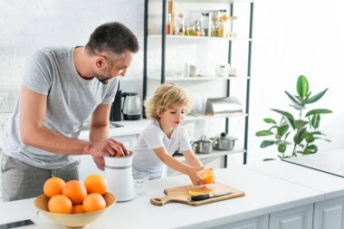 happy family making fresh orange juice by squeezer on table at kitchen