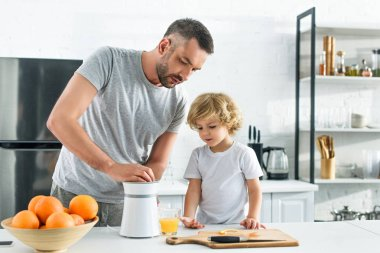 focused father and little son making fresh orange juice by squeezer on table at kitchen