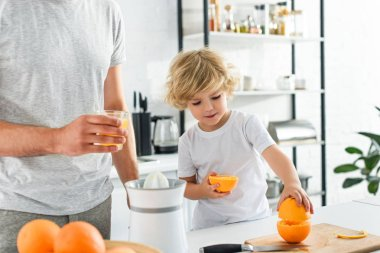cropped image of father with glass of fresh juice and his son taking orange from cutting board at kitchen