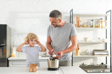 little boy closing ears by fingers while his father breaking for making dough at kitchen