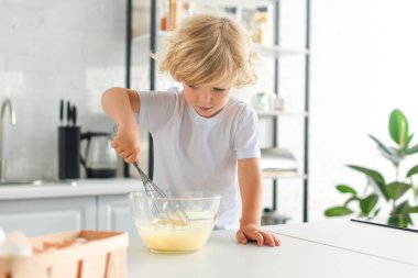 little boy making dough by whisk on table at kitchen