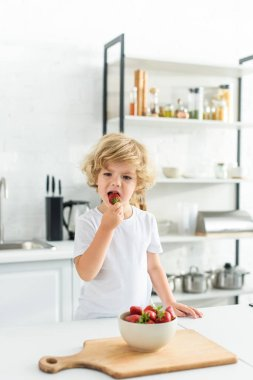 adorable little boy eating strawberry near table on kitchen