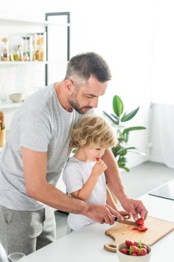 father cutting strawberry by knife while his son standing near and eating strawberry at kitchen