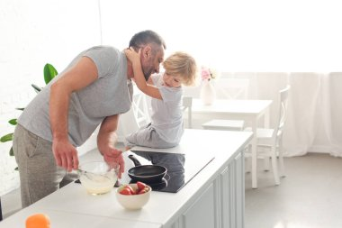 son hugging smiling father while he whisking dough in bowl at kitchen