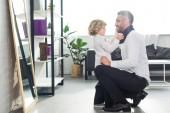 Fotografie boční pohled malého chlapce pomoc otce vázání kravaty doma