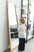 Photo rear view of little boy tying necktie over white shirt in front of mirror at home