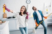 Photo girlfriend and boyfriend in rubber gloves singing and playing mop like guitar in kitchen