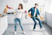 Photo girlfriend and boyfriend in rubber gloves having fun with mop in kitchen