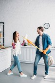 Photo couple in rubber gloves having fun with mop and pretending singing in kitchen
