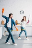 Photo couple in rubber gloves having fun with mop and dust brush in kitchen
